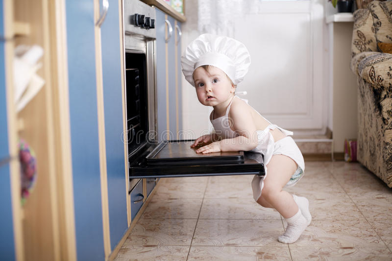 Baby chef cooks in the oven food royalty free stock images