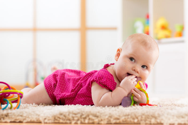 Baby chewing on teething toy. Baby girl 7 months chewing on teething toy royalty free stock images