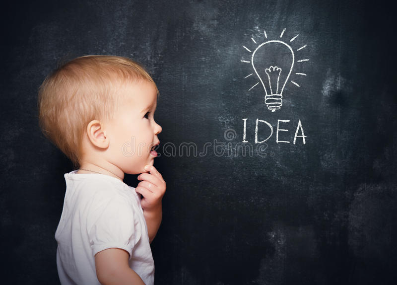Baby child at the blackboard with chalk drawn bulb symbol ideas. Baby child at the blackboard with chalk drawn light bulb symbol ideas royalty free stock photography