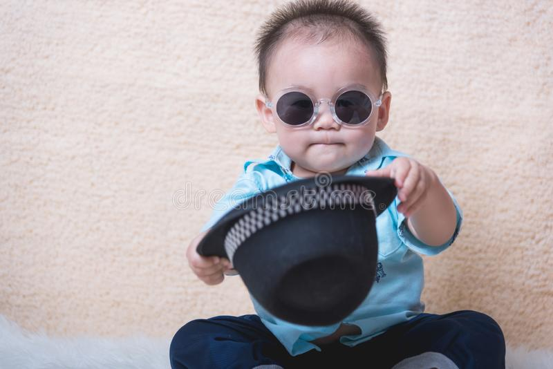 Baby child boy fashion. Sitting with sunglasses royalty free stock image