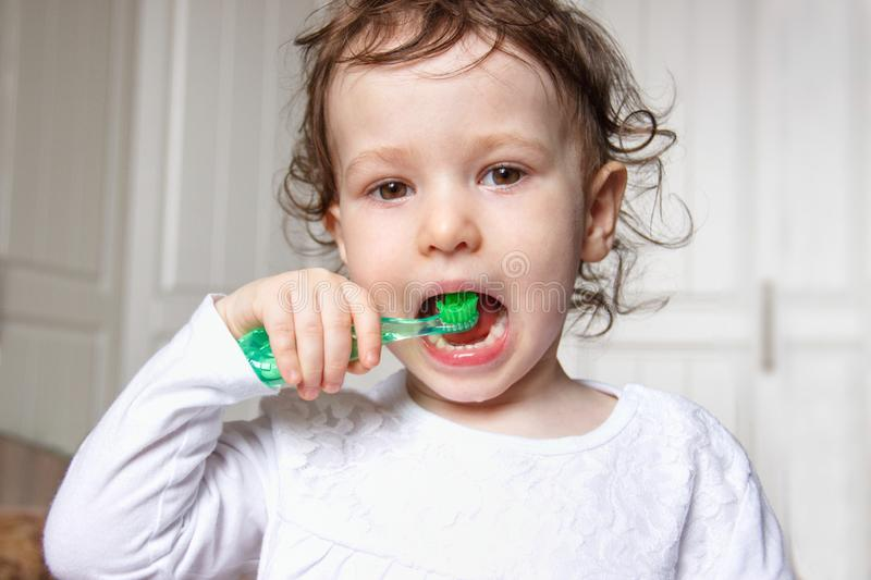 Baby child brush their teeth properly with a green toothbrush royalty free stock photography