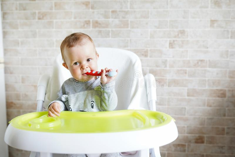 Baby child eating with spoon in sunny kitchen. Portrait of happy kid in high chair. copy space royalty free stock photos