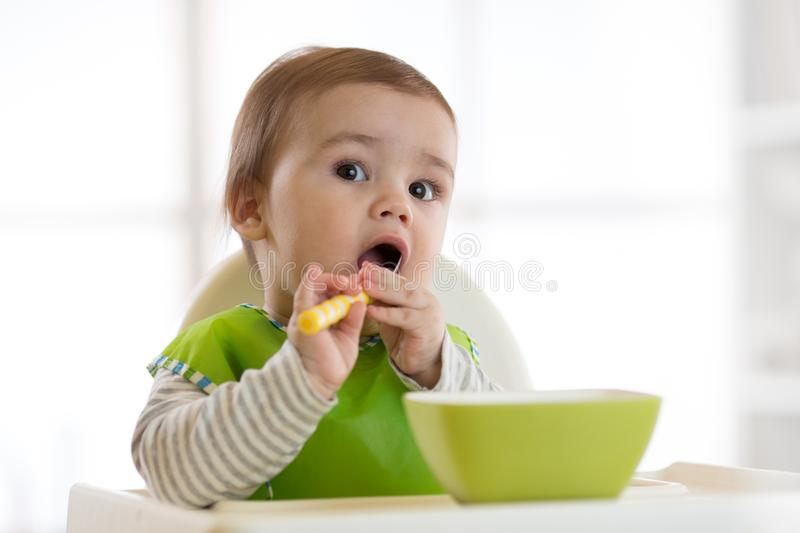 Baby child eats food himself with spoon. Portrait of happy kid boy in high chair. stock photos