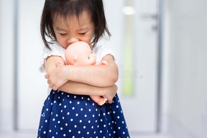baby child holding baby doll afraid to walk out the door stock photos