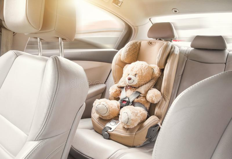 Baby child seat car. A beige teddy bear is fastened with seat belts in a car seat. Travel by car.  stock photos