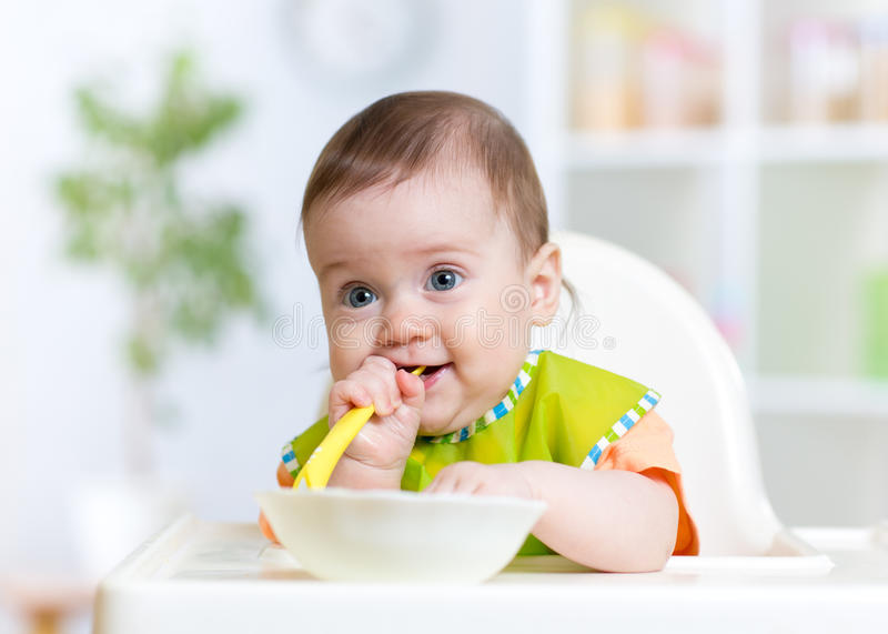 Baby child sitting in chair with a spoon stock photography