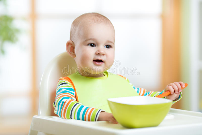 Baby child sitting in chair with a spoon. Happy baby child sitting in chair with a spoon royalty free stock photos