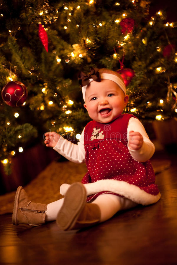 Baby by Christmas Tree. 7 month old baby laughing by Christmas Tree on wood floor stock image