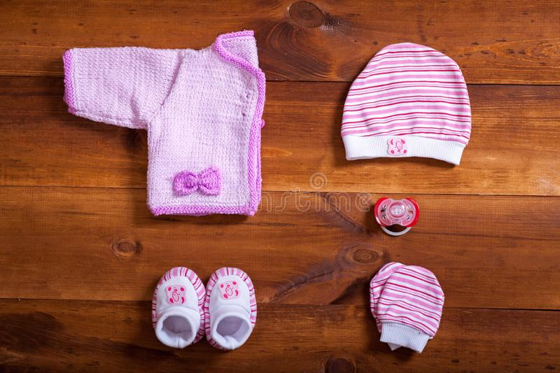 Baby clothes and accessories on brown wooden background table, pink child newborn fashion clothing set for girl, modern kid infant stock images