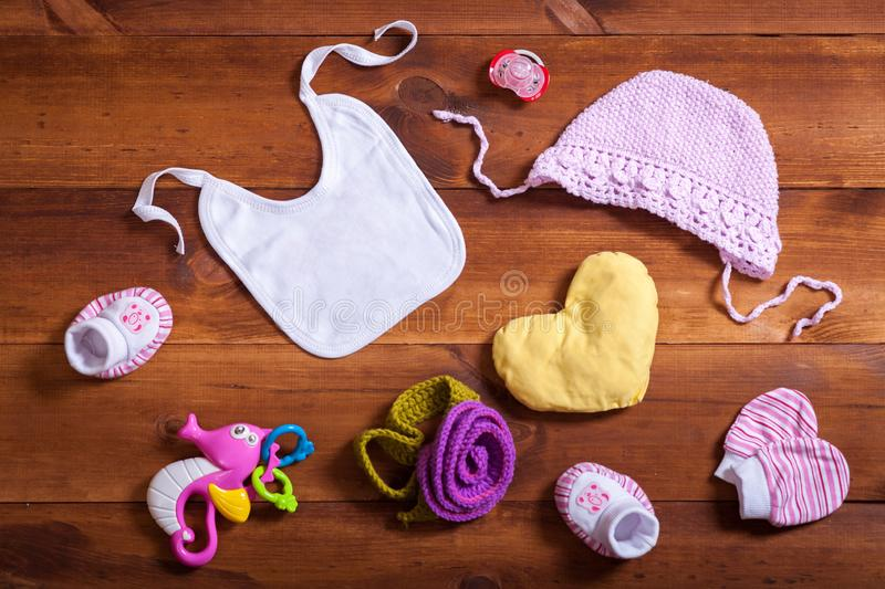 Baby clothes accessories set, pink knitted cotton clothing, toys and kid bib on brown wooden background, child newborn fashion stock photography