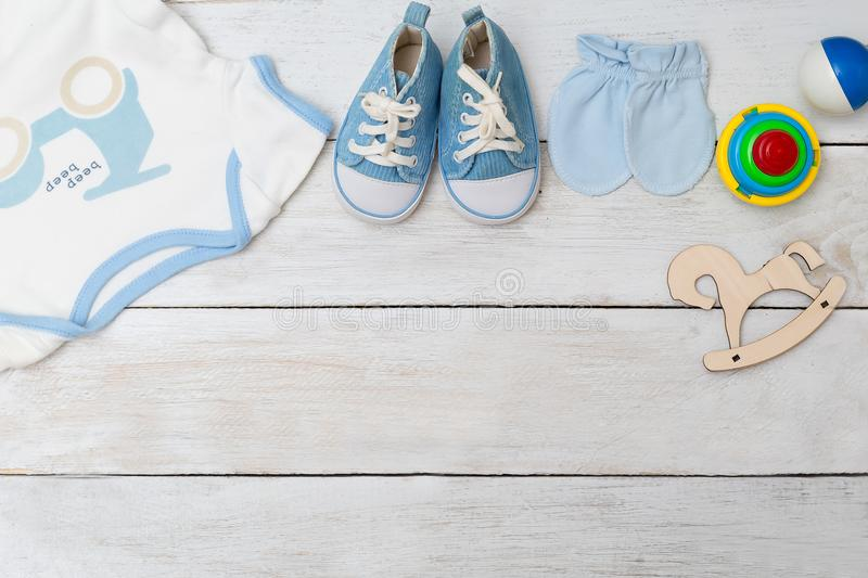 Baby clothes and baby shoes for boy on wooden background. Copy s stock photo