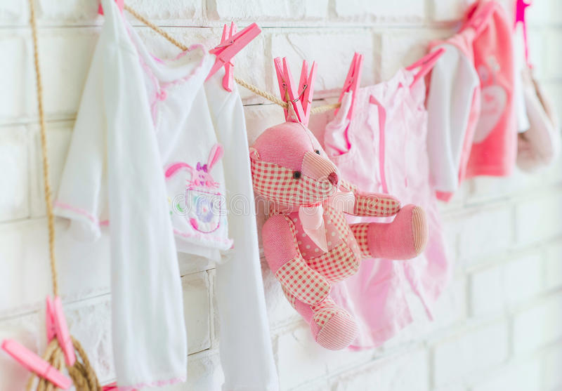 Baby clothes and bear toy hanging on the wall. As decoration side view royalty free stock image