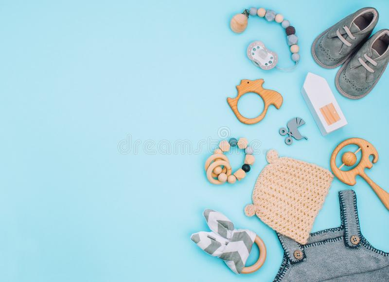 Baby clothes, booties, soother and wooden toys on light blue background royalty free stock photos