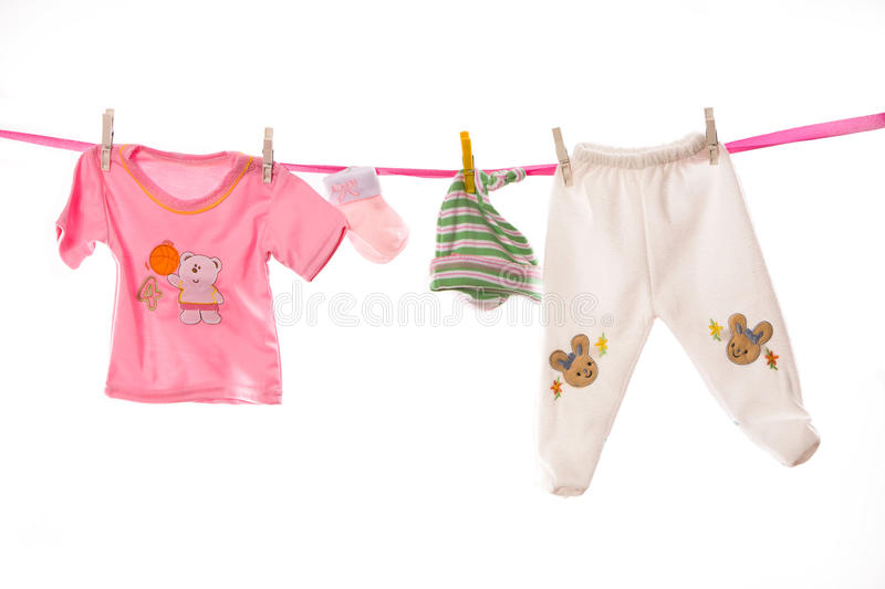 Baby clothes on a clothesline. Girl baby clothes on a clothesline isolated on white stock photos