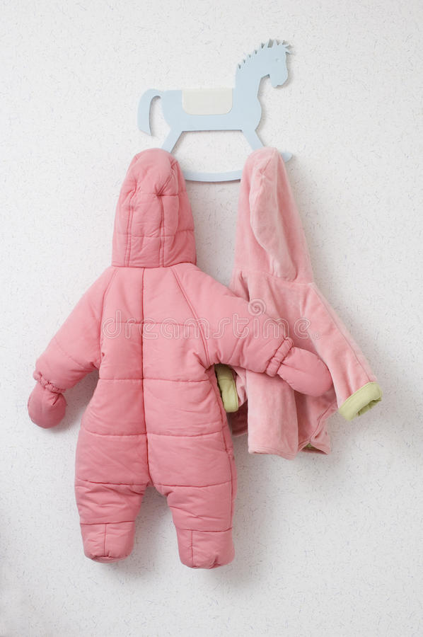 Baby clothes on a coat rack. Nursery and baby pink clothes on a coat rack royalty free stock photography