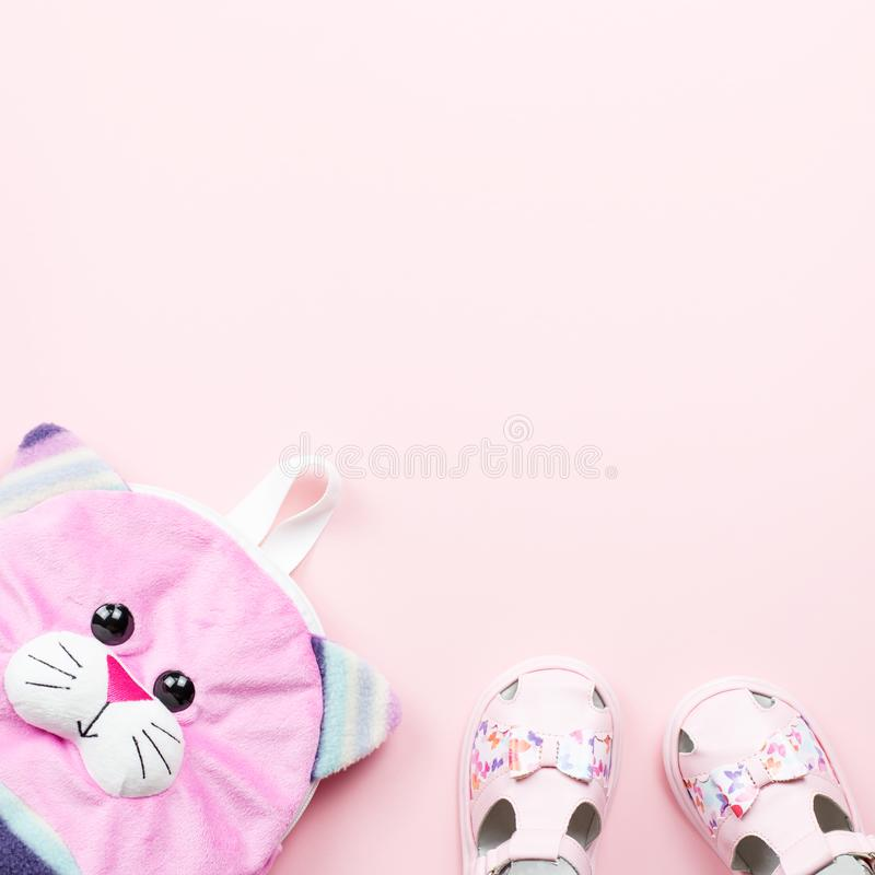 Baby clothes collection flat lay with sandals, backpack on pastel background royalty free stock images