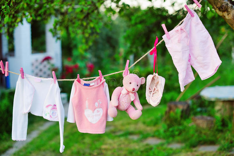 Baby clothes drying outdoors stock photography