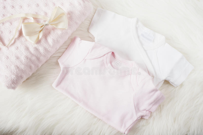 Baby clothes for a girl. Baby jumpsuits, rompers, bow hair band and pink diaper. On a white fur carpet. Newborn baby concept. Baby royalty free stock images