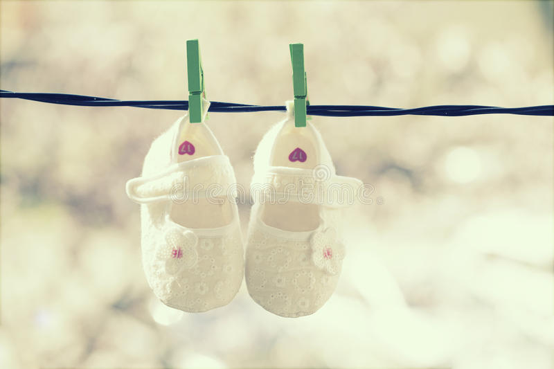 Baby clothes hanging on the clothesline. Baby shoes hanging on the clothesline stock images