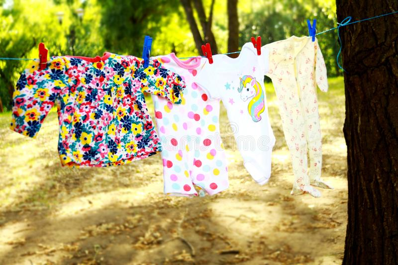 Baby clothes hanging on rope stock photos