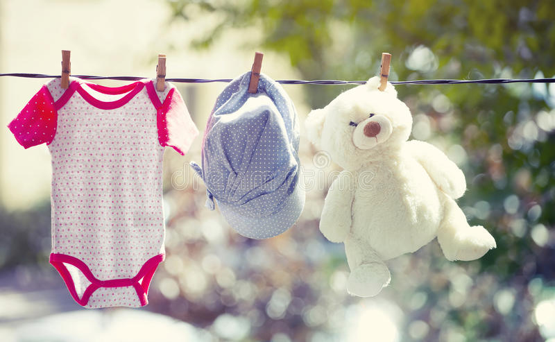 Baby clothes, hat and teddy hanging on the clothesline. Baby clothes, hat and teddy bear hanging on the clothesline - family concept, newborn concept royalty free stock images