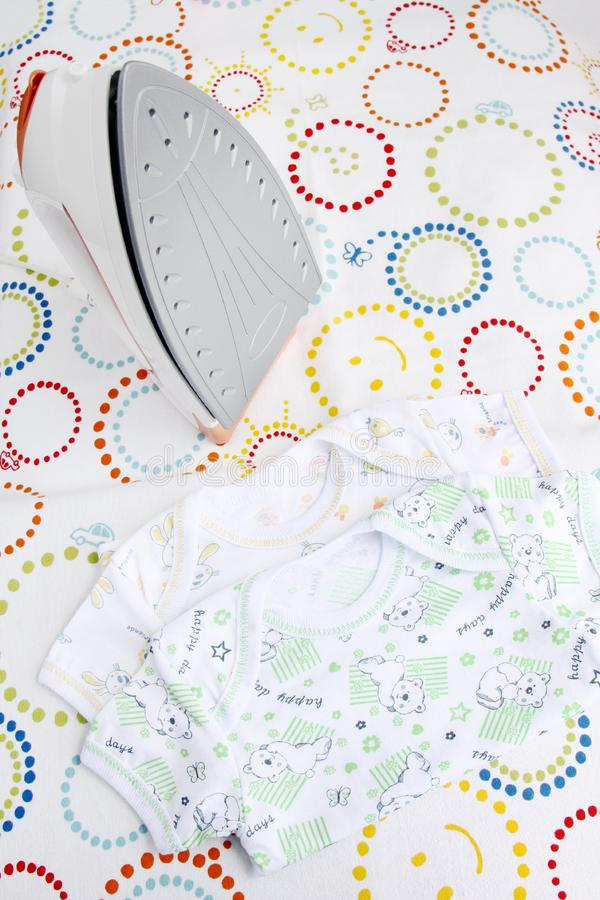 Baby clothes and iron on ironing board on colorful background with copy space stock images