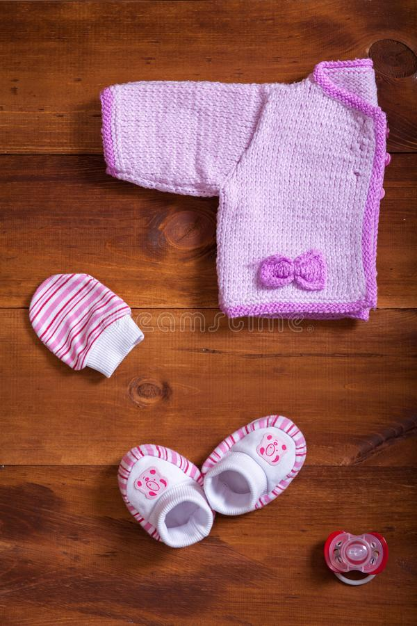 Baby clothes pink knitted sweater cotton mittens socks and dummy on wooden background, infant cloth set on table, child newborn royalty free stock images