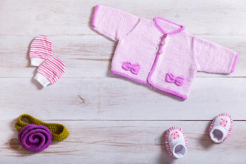 Baby clothes pink knitted tiny sweater cotton little mittens socks on white wooden background, infant cloth set on table, child stock photos