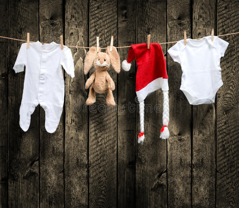 Baby clothes and santa hat on a clothesline. Wooden background stock image