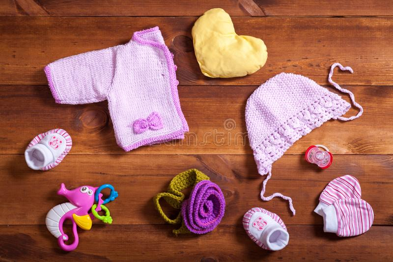 Baby clothes set concept, pink knitted clothing, toys and accessories on brown wooden background, child newborn fashion cloth for stock photos