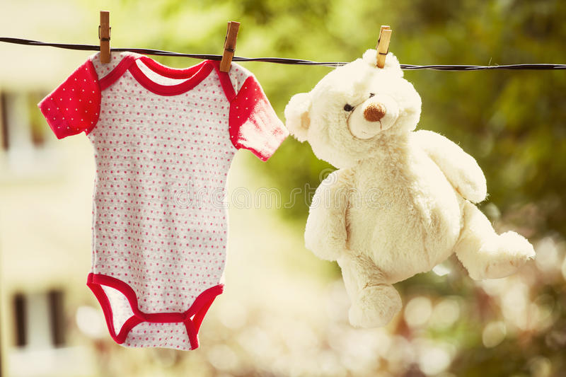 Baby clothes and teddy bear hanging on the clothesline. Family concept stock images