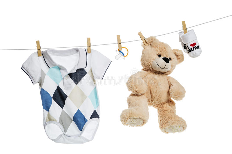 Baby clothes and teddy bear hanging on the clothesline. On white background royalty free stock photos