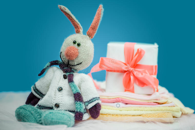 The baby clothes with a white gift box. On blue background stock photography