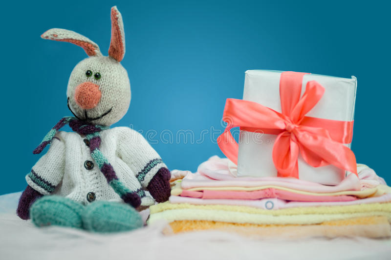 The baby clothes with a white gift box. On blue background stock photos