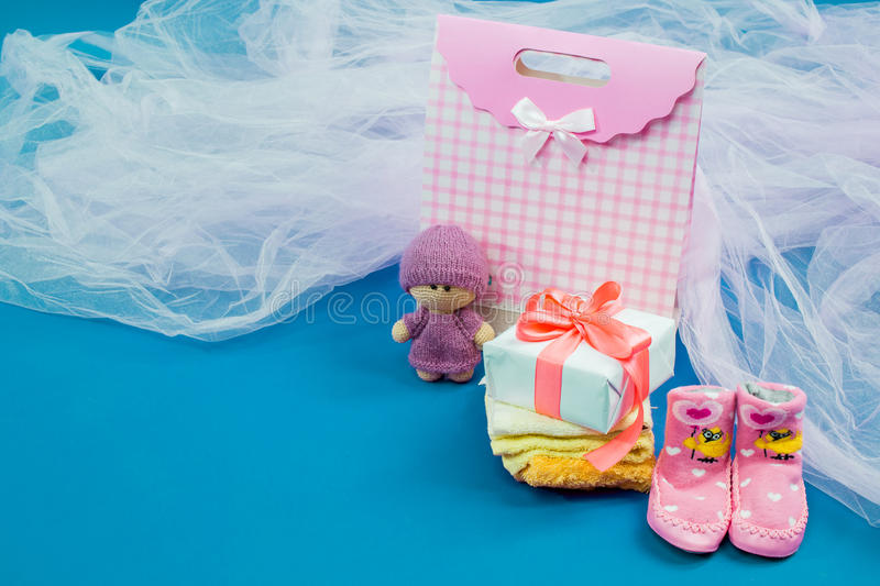 The baby clothes with a white gift box. On blue background stock image
