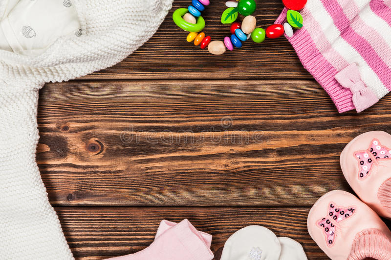 Baby clothes on wooden background.  stock photos