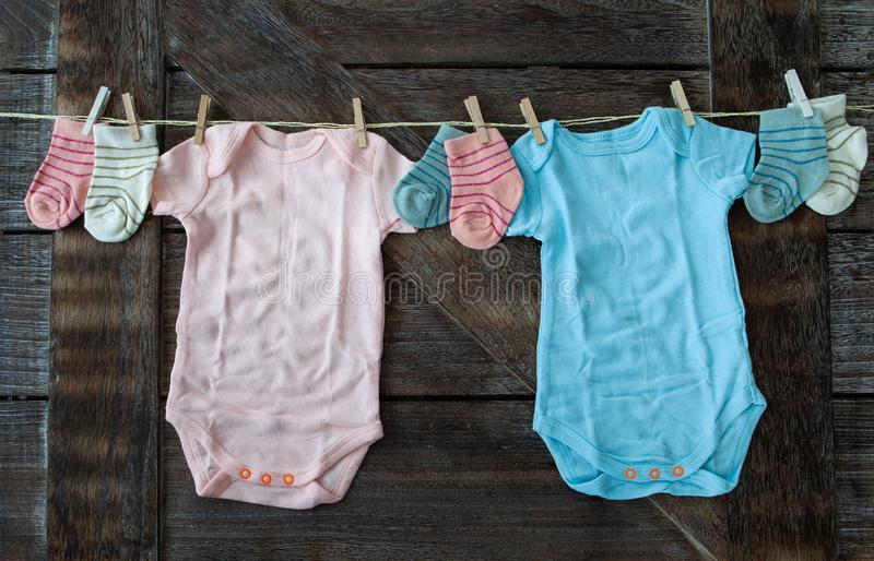 Baby clothing in pink and blue. On rustic wooden background stock image