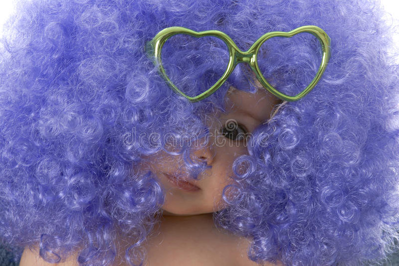Baby clown. Seven month old baby wearing clown wig with heart shaped glasses stock image