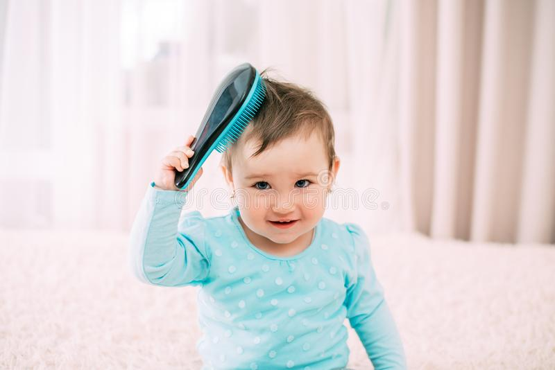 Baby with a comb a little girl with a blue comb comb combs her hair royalty free stock photography