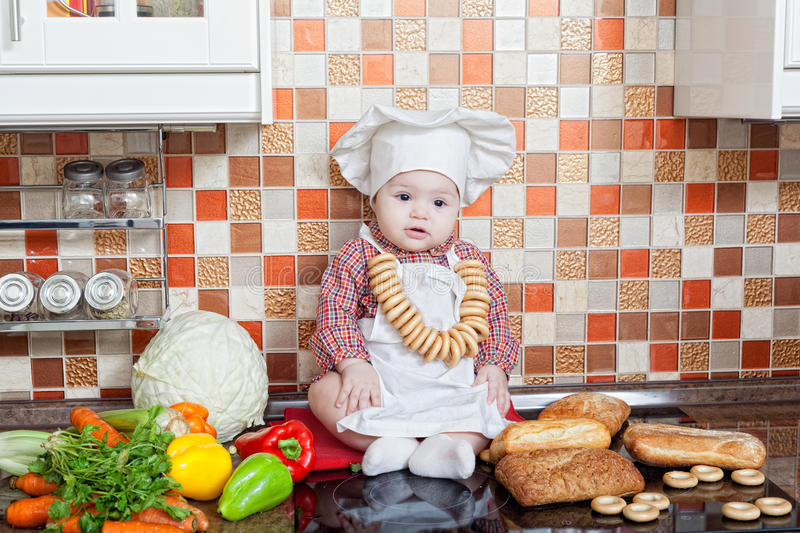 Baby cook with bread. And steering-wheels sits on a kitchen table stock photography