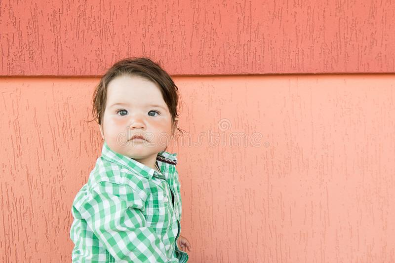 Baby on a coral background. Little boy. in a checkered green and white shirt stock images