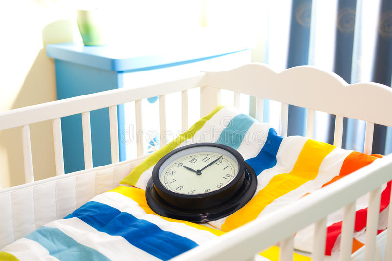 Baby cot. With clock as concept of awaiting and colorful blanket stock photo