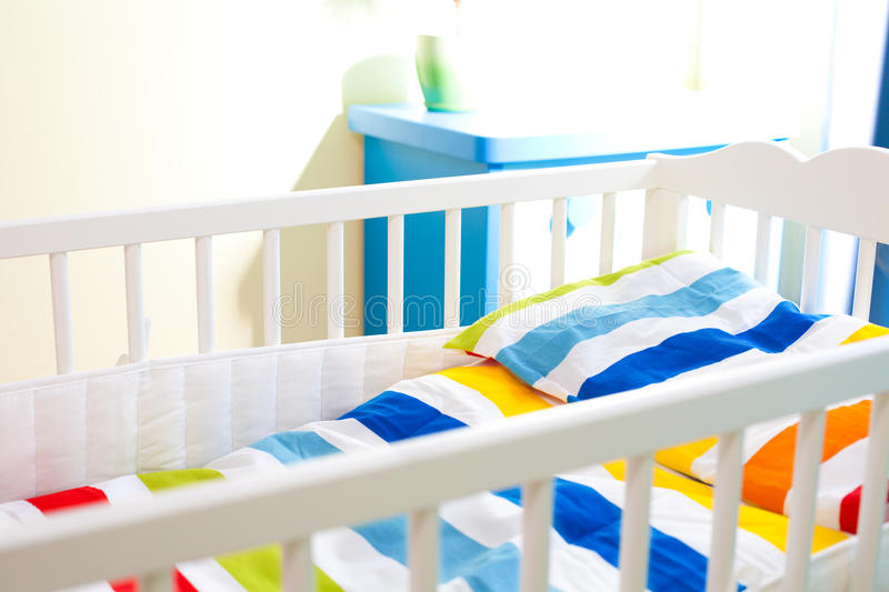 Baby cot. With colorful blanket in nursery room royalty free stock photo