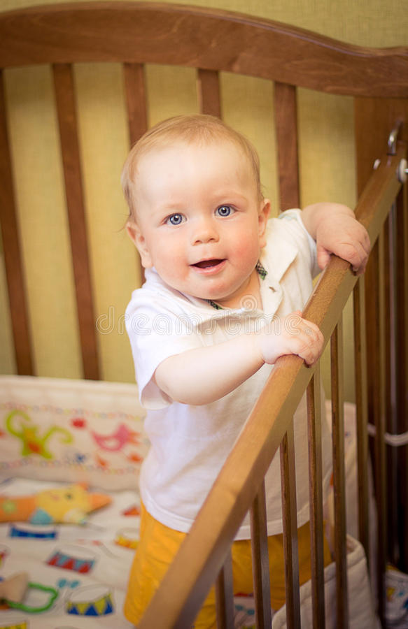 Baby in cot. Babyboy standing in a cot stock photo