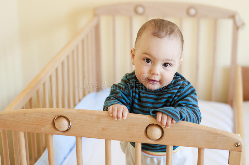 Baby in cot. Cute 8 month old baby, boy or girl standing in wooden cot or crib royalty free stock image
