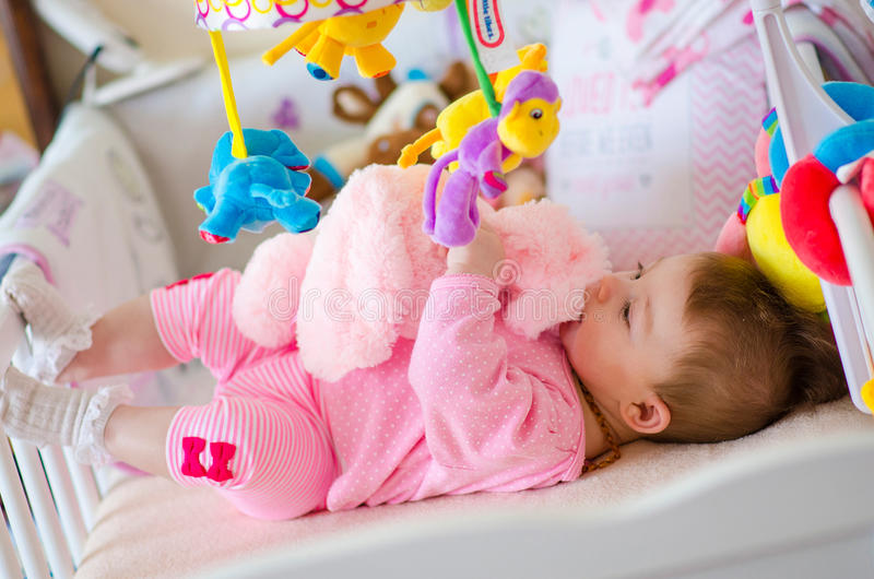 Baby in a cot. Little cute baby girl playing in a cot stock images
