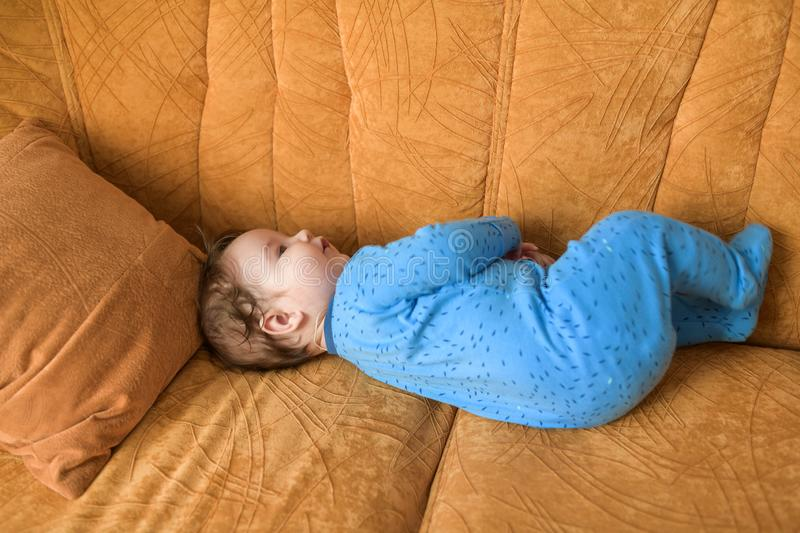 Baby on the couch. Happy baby lay idle. Portrait of a lovely laughing and blue shirt lying on a couch and looking up stock photos