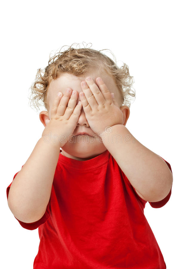 Baby covering eyes with hands playing peek-a-boo. Portrait of a child playing peek a boo game, covering her eyes with her hands, in red clothes, isolated on pure stock photos