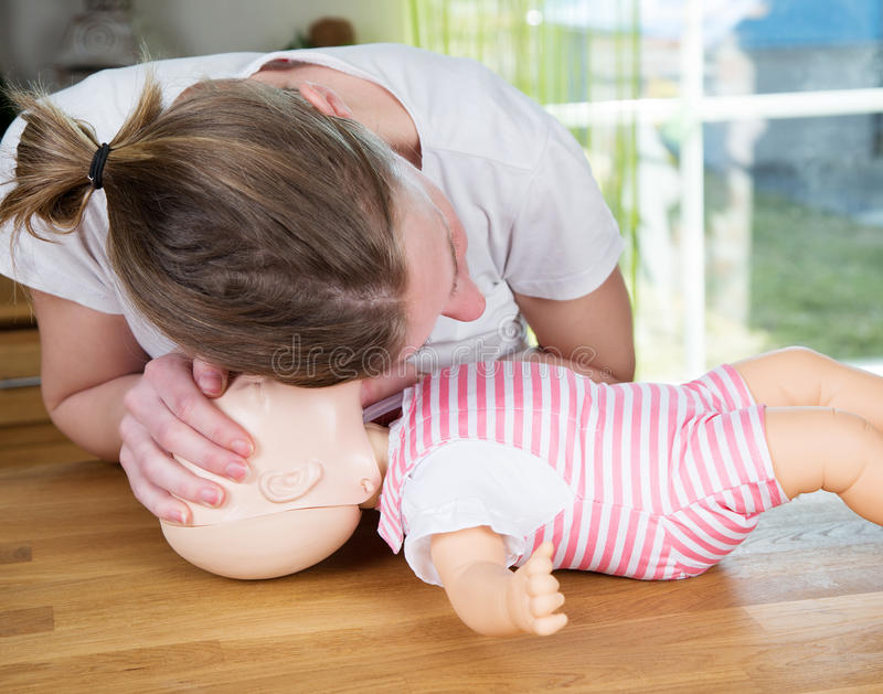 Baby CPR check for signs of breathing stock photo