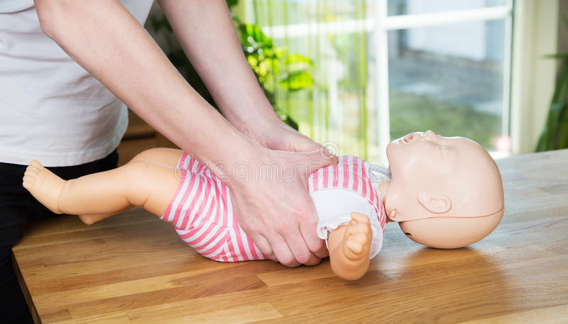 Baby CPR two hand compression stock images
